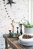 Candlesticks and wintry decorations on table in front of brick wall