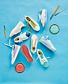 Various sneakers, paint lids and brushes on a blue background