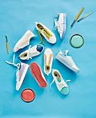 Verschiedene Sneakers, Farbdeckel und Pinsel auf blauem Untergrund