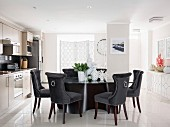 Elegant velvet-covered chairs around designer table in bright kitchen
