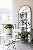 Bistrotisch und Stühle vor grossem Wandspiegel auf dem Balkon