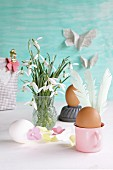 Eggs decorated for Easter with feathers and paper flowers next to vase of snowdrops