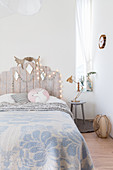Bed with wooden headboard in child's wintry bedroom