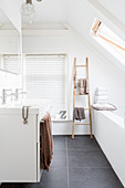 Towels on wooden ladder in modern attic bathroom