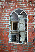 Madonna figurine behind old arched window in brick wall