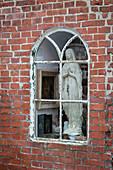 Madonnenfigur hinter altem Bogenfenster in Backsteinwand