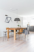 Wooden table and various vintage chairs on pale wooden floor