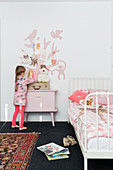 Girl in front of bedside cabinet in child's bedroom with pink accents
