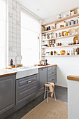 Kitchen accessories in shades of brown on wall-mounted shelves in kitchen with grey cabinets