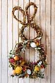Bunny-shaped Easter wreath decorated with flowers on wall