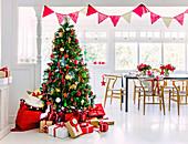 Verpackte Geschenke um den Weihnachtsbaum vor dem Esstisch