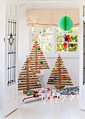 Christmas trees made of wooden slats with colorful paper decorations