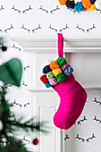 Pink Christmas stocking with pompoms on the fireplace console