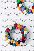 Colorful wreaths of pompoms on the wall with antlers pattern