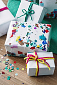 Colorfully wrapped presents with confetti and colored strings