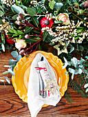 Gedeck mit gelbem Teller und festliche Blumendekoration auf Tisch