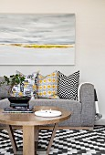 Landscape painting above grey couch with various scatter cushions