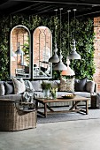 Wicker furniture in front of arched mirrors on climber-covered wall on terrace