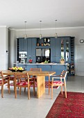 Solid wooden furniture in dining area of open-plan country-house kitchen with blue fronts