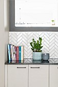 White kitchen counter with white herringbone-tiled splashback
