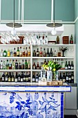 Bar counter with hand-painted tiles on front and shelves of bottles