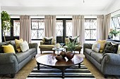 Classic living room in natural shades with bank of large windows