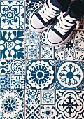 Sneakers on blue and white floor tiles with various patterns