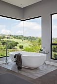 White free-standing bathtub in front of frameless, panoramic corner window with view of landscape