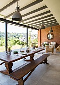 Long wooden dining table and bench in front of lounge area in interior with glass wall
