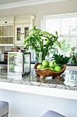 Green apples in fruit bowl, candle lantern and vase of white lilies on kitchen worksurface