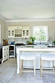 White stools and island counter in front of wall-mounted cabinet next to window in kitchen in French country-house style