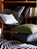 Floor cushions next to designer chair in front of bookcase