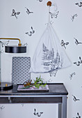 Cloth bag printed with fern leaf hung on wall with butterfly-patterned wallpaper