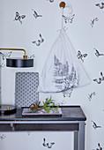 Mit Farnblatt bedruckter Stoffbeutel an der Wand mit Schmetterlingen