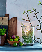 Pressed fern leaf in candle lantern amongst rustic accessories made from natural materials