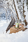 Besom broom leant on sack of presents in snowy landscape