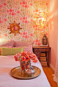 Flowers and teapot on tray in romantic bedroom
