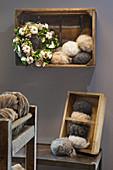 Kranz mit Baumwollkapseln in einer Holzkiste als Wandregal