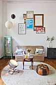 Eclectic furniture on round rug below arrangement of pictures on wall in living room