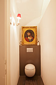 Picture of Jesus in gilt frame on ledge above round toilet