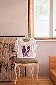 T-shirt pulled over back of old Baroque chair below window