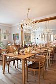 Gedeckter Tisch mit verschiedenen Stühlen vor verspiegelter Wand