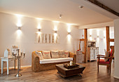 Wall lamps above wicker sofa next to exposed structural timbers