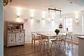 Old shabby-chic furniture: chairs and bench around dining table
