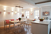 Shabby-chic dining room furniture next to modern kitchen island