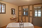 Modern bathtub in bathroom with old half-timbered wall