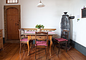 Biedermeier chairs around wooden table next to old iron stove