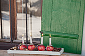 Advent arrangement of candles stuck in numbered apples