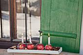 Kerzen stecken in nummerierten Äpfeln als Adventskranz