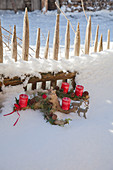 Advent arrangement of gnarled wood and red candles in snow